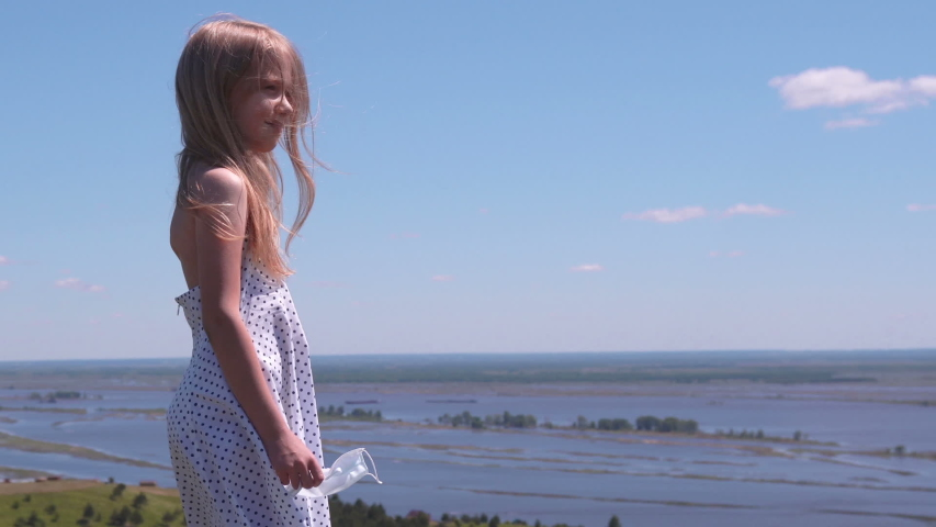 Blonde pretty girl admires the panorama of the river flood from the top of the hill on a clear summer day. The girl comes closer, removes the mask and looks at the beautiful river landscape around. Th