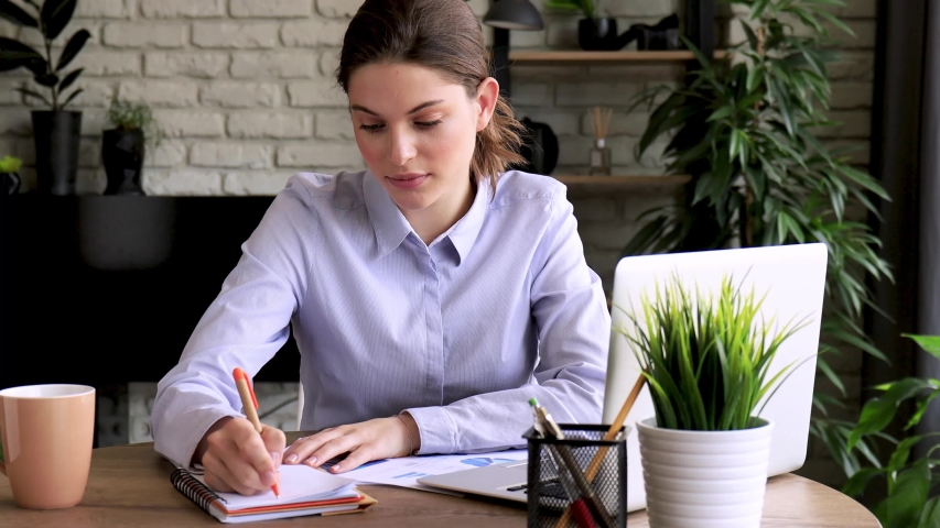 Beatiful girl student studying on laptop writing notes. Busy attractive businesswoman in the office. Royalty-Free Stock Footage #1054354865