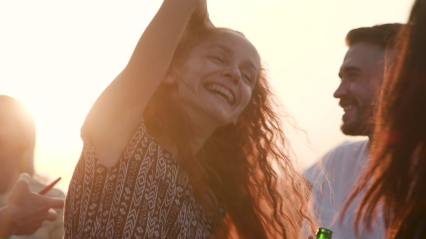 Fun Social Group Young Girls and Guys Arms Raised Enjoy Nature Outdoor. Recreation Happy Laughter 30s Woman Listen Music and Dance on Summer Sunset. Meeting Energy Moving People with Glass Drink 4k