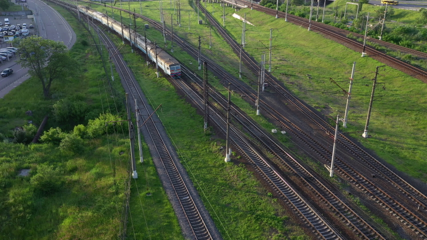 Several railways in the city. A train with wagons rides on rails. Aerial drone shot over railway. Aerial view of railroad with train. 4K UHD Shot on Mavic 2 Pro Drone. | Shutterstock HD Video #1054356260