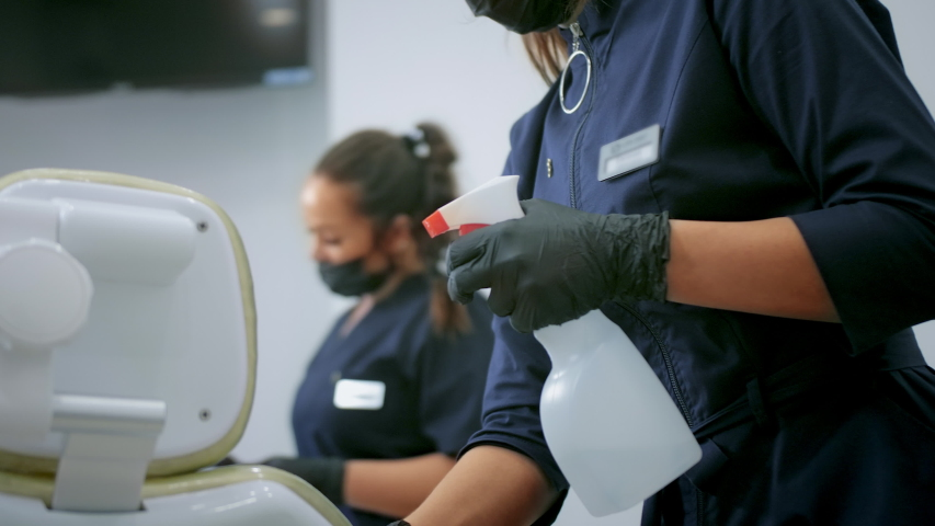 Good people is sanitizing dentist chair by disinfectant to fight corona virus. Women make disinfection of Covid-19 for healthcare. Girls disinfect room with sanitizer against coronavirus covid 19. Royalty-Free Stock Footage #1054356725