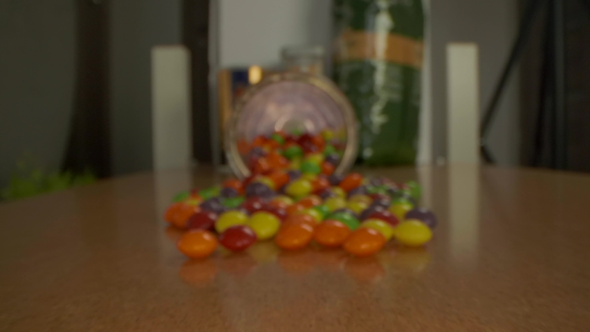 Pan over round candy sweets on a wooden table. View goes right into the glass jar.  | Shutterstock HD Video #1054356764