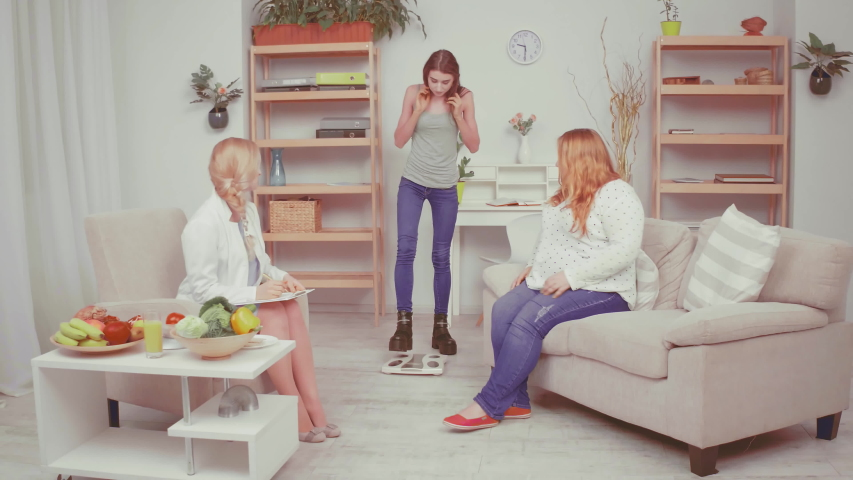 Doctor ask bulimic girl to do body weight talking about low weight problem and consults about health issues with her friend overweight girl. Healthy food concept. Tinted video. Prores 422.