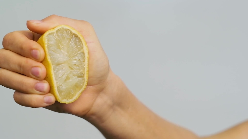 Woman's hand squeezing a half of a lemon. Half of juice lemon in hand.