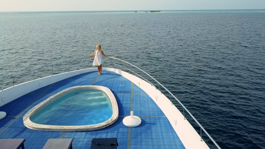 Beautiful adult woman in flowing white dress stand on deck of luxurious expensive yacht. Vacation or holiday goer tourist enjoy pacific ocean on rich people retreat, white cruise boat with deck pool  Royalty-Free Stock Footage #1054358957
