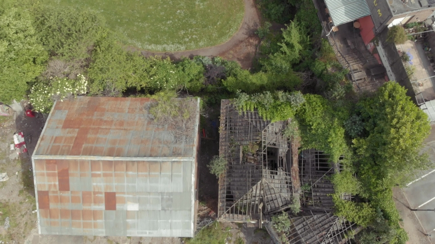 Birds eye view of derelict abandoned building overgrown with weeds | Shutterstock HD Video #1054359050