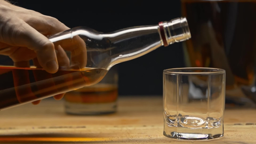 Cropped view of man pouring whiskey into glass isolated on black | Shutterstock HD Video #1054359464