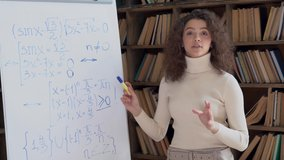 Hispanic school teacher give math class look at camera explain equation point at whiteboard stand in classroom. Online class, video conference call virtual teaching, distance lesson. Webcam view