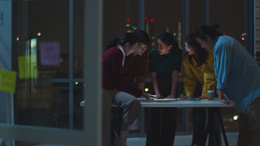 Group of Asia young creative people in smart casual wear discussing business brainstorming meeting ideas mobile application software design project in modern night office. Coworker teamwork concept. Royalty-Free Stock Footage #1054360478