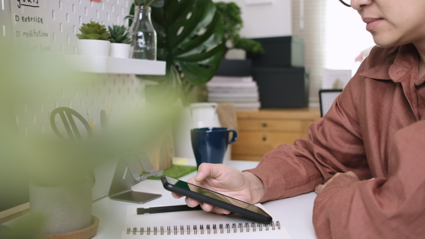 Close up of a woman's hand holding a mobile phone, and swiping screen  ,at the desk in cozy home atmosphere , workplace in room decorated with green  plants,working from home  office.