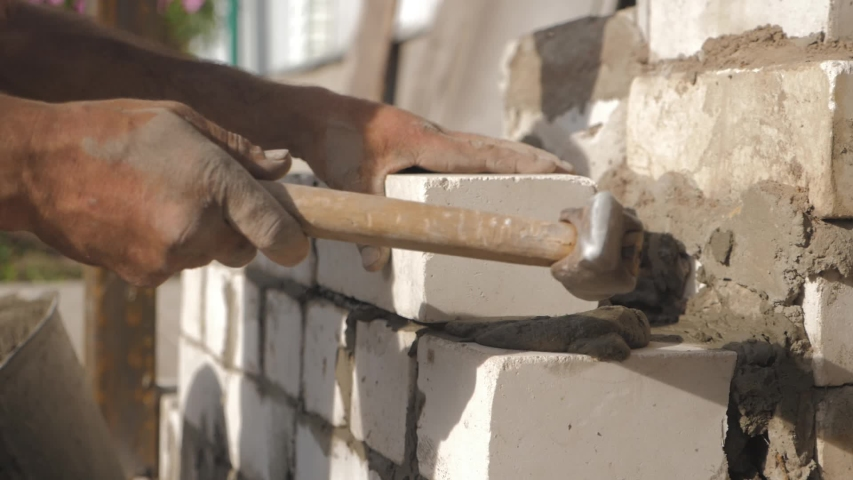 Construction worker or mason laying bricks and creating walls. Bricklayer laying bricks to make a wall. Building a cement block wall for a house. | Shutterstock HD Video #1054361363