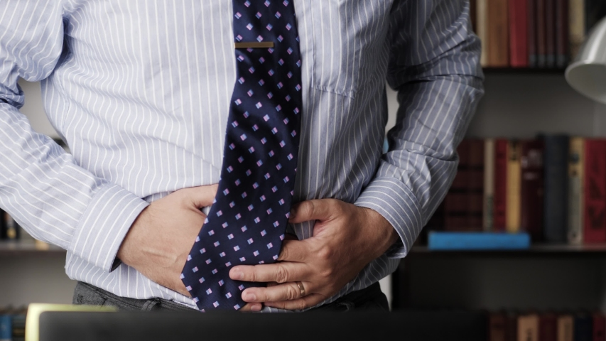 Stomach pain. Close-up of bearded man in workplace experiencing pain in his stomach and getting up from chair. Diarrhea, constipation, irritable bowel concept | Shutterstock HD Video #1054361822