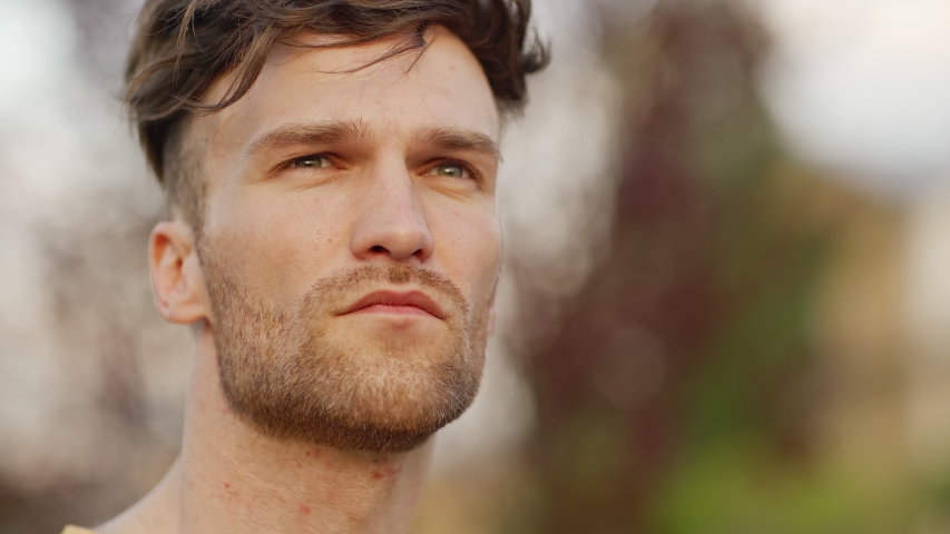 Closeup portrait of serious handsome young man with stubble looking around while waiting for somebody standing outdoors in park, copy space to right | Shutterstock HD Video #1054364231