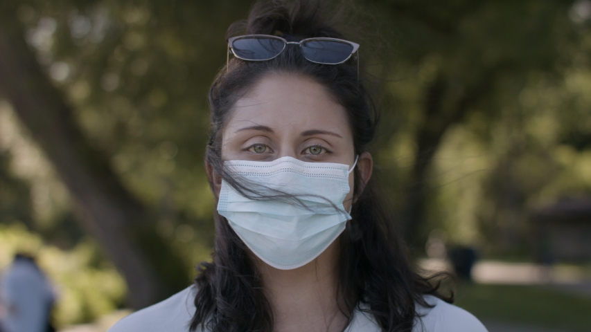 Authentic portrait of a young woman wearing a medical mask in a beautiful public park. Shot in 4k  Royalty-Free Stock Footage #1054365368