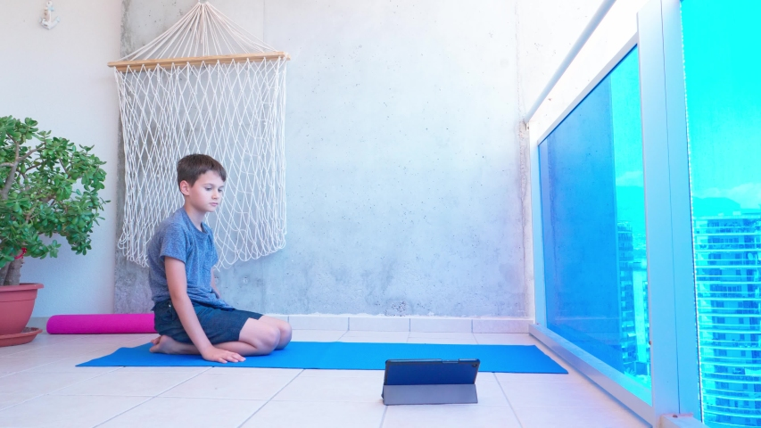 Kid doing sport exercises, doing plank exercise on yoga mat while watching video lesson online on tablet computer on balcony. Sport, healhty lifestyle, active leisure at home | Shutterstock HD Video #1054366739