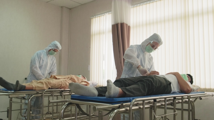 Coronavirus affected patient lying on stretcher having first aid cure by emergency paramedic doctor with PPE suit and mask with face shield to prevent from Covid pandemic. Illness man having dry cough   Shutterstock HD Video #1054366775