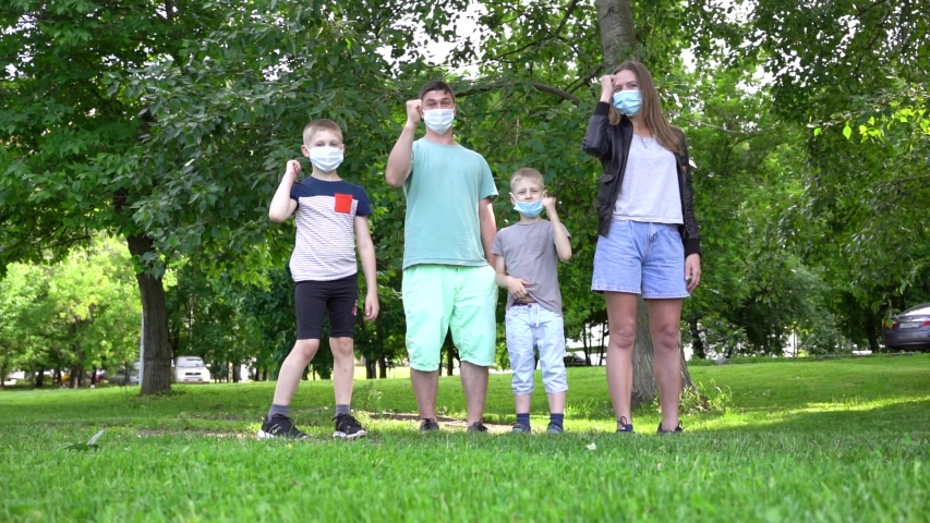 Happy masked family of four. Mom, dad, two sons stand in the park and show their thumb. End of quarantine. Safety in public places.   Shutterstock HD Video #1054367096