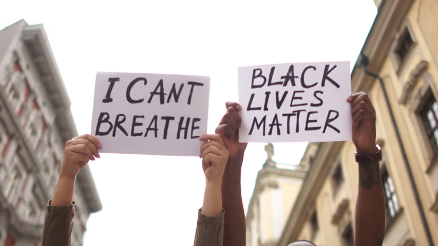 Protests against racism and discrimination in the US and Europe. Young african man and caucasian woman holding a cardboard posters with the message text I CANT BREATHE and BLACK LIVES MATTER