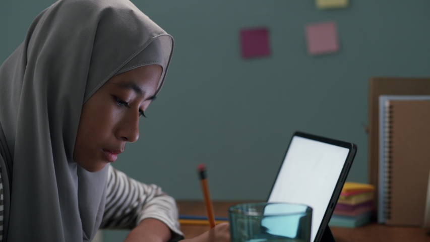 homeschooling. Muslim little girl is studying online via the internet with tablet on the desk at night. Asia elementary children write homework. Concept distance learning at home Royalty-Free Stock Footage #1054368431
