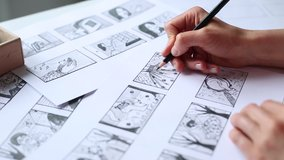 Hands of the artist designer draw a storyboard on paper. Storytelling. Story frames with heroes.