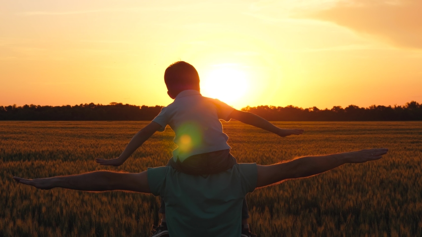 Father holding son on shoulders, imitating the flight of the aircraft. Silhouette of a happy family at sunset. The concept of generations, education of children, freedom. | Shutterstock HD Video #1054369019