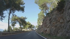 4K POV footage of car driving on winding road along the coast of Mediterranean sea, pine trees and beautiful mountain landscape. Mallorca island, Spain. Slow motion video during sunny day