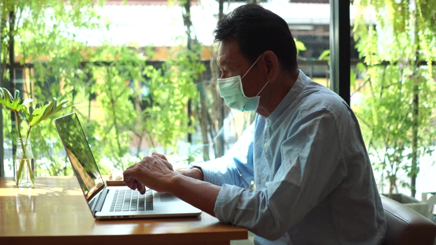 Old man using laptop computer in cafe and wearing mask for prevent the spread of the Covid-19, Covid-19 virus protection concept in Thailand. | Shutterstock HD Video #1054370969