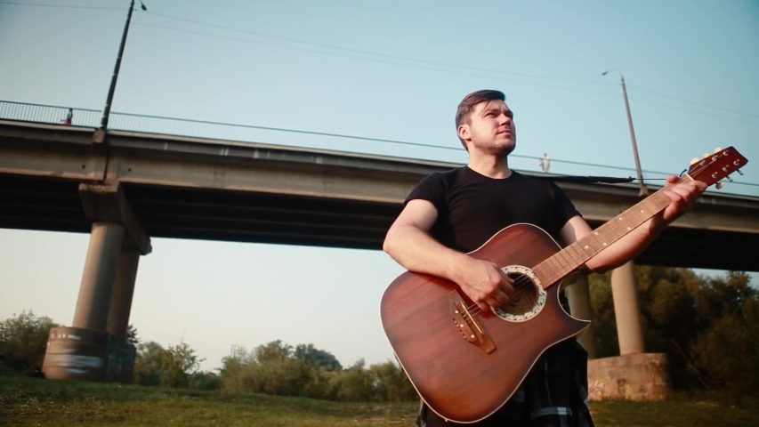 A young man in a black T-shirt stands on the background of the bridge and plays the acoustic guitar.