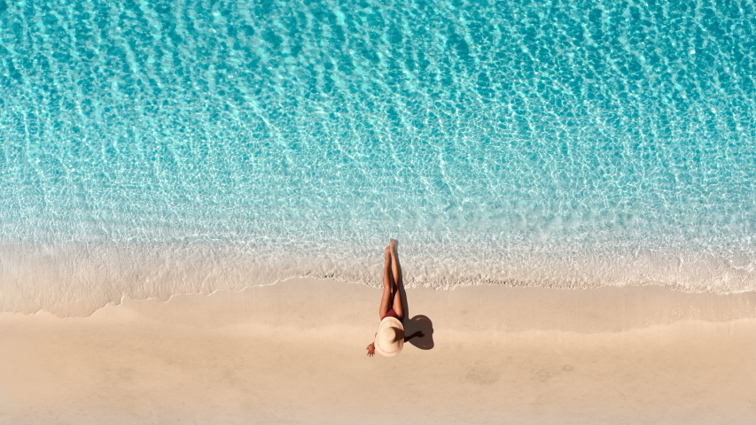 Beautiful young blonde woman at luxury hotel resort celebrating summer vacation. Aerial view of sand beach. Girl enjoying sunny day on travel holiday. Perfect for summer background. Tropical beach.