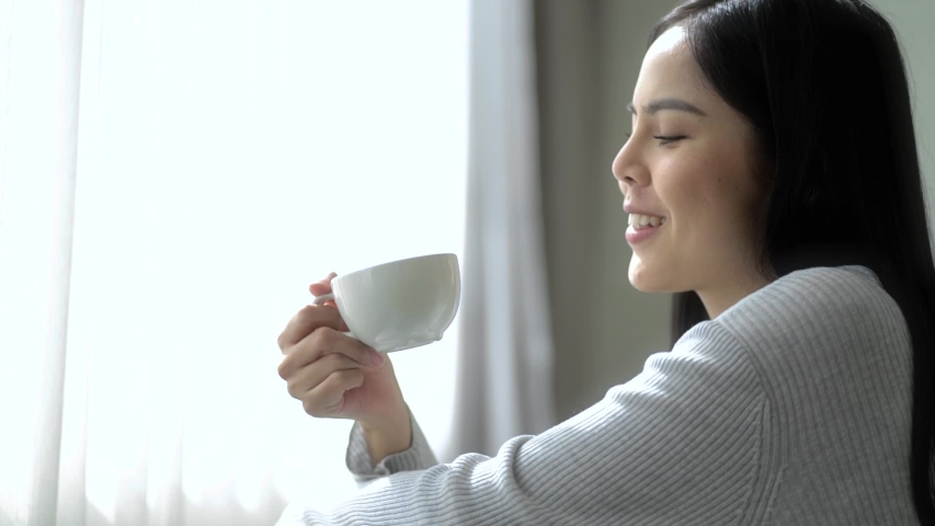Close up young asian woman looking out window enjoying fresh new day feeling rested and drinking coffee at home. Slow Motion Full Hd. Royalty-Free Stock Footage #1054373519