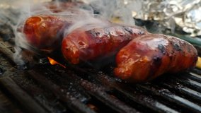 close-up view of tasty sausages grilling on charcoal grill