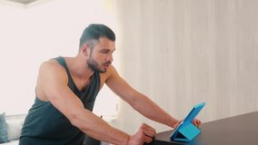 Young man exercising at home. Fitness trainer explain how to do right workouts and exercise at home through video call on tablet. Cheering and doing congratulations.