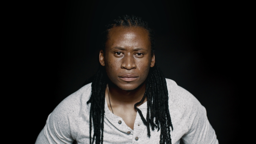 African male with dreadlocks on black background. Muscular man looking at camera.