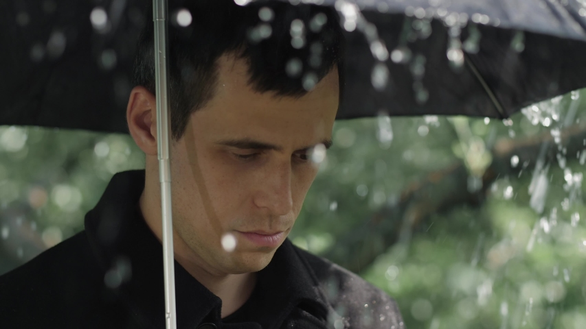 Man under umbrella at the funeral | Shutterstock HD Video #1054375781