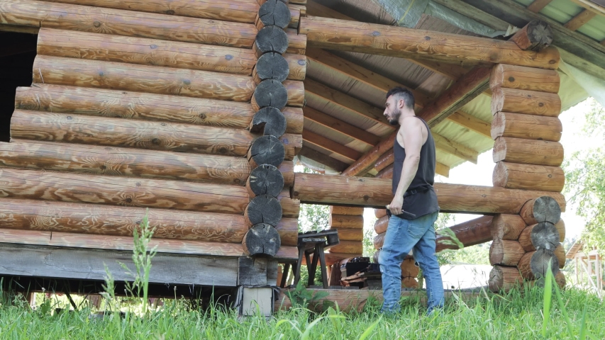 A male carpenter comes to a log wall and begins to caulk. With a chisel, he breaks through a gap of gaps between the logs. UHD video. | Shutterstock HD Video #1054378496
