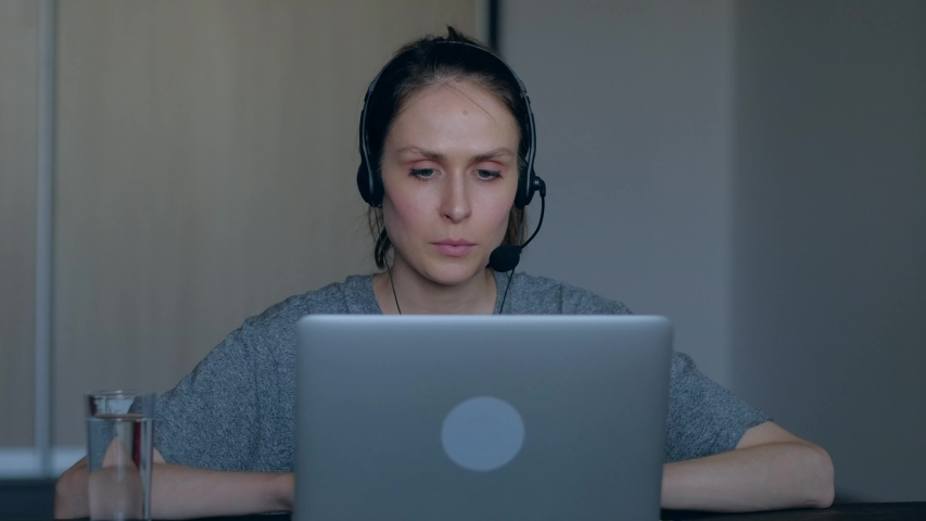 Angry mad woman customer service representative working in home annoyed stressed talking with client use headset, drink water from a glass. 4k. Feeling stressed on the job. | Shutterstock HD Video #1054378622