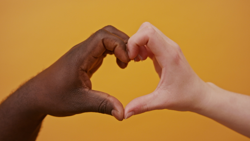 black and white hands forming heart shape together isolated on the orange background. Close up. Royalty-Free Stock Footage #1054379435