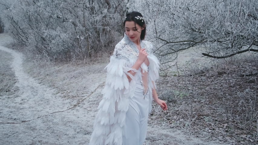 Beautiful fantasy woman walking in carnival costume snow queen. White creative cape cloak, silver tiara, diadem, bird white feathers dress. Image greek goddess angel. winter nature snowy trees, forest
