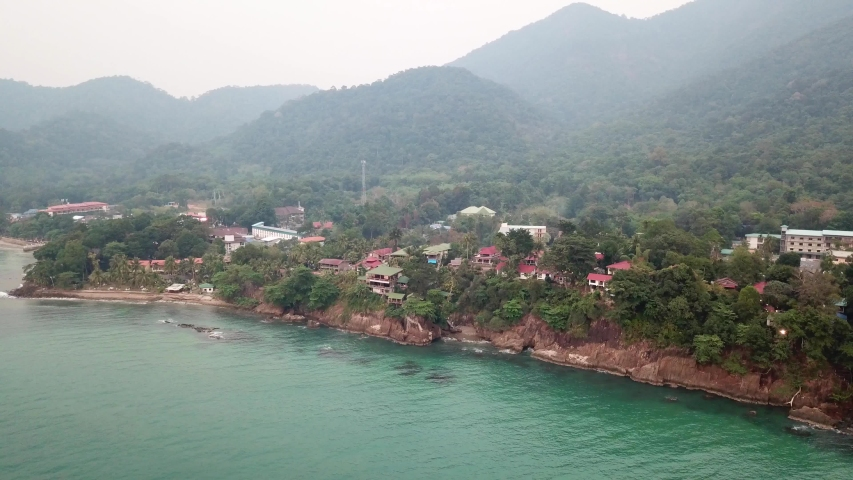 Green Chang island is covered in smoke from a fire in Cambodia. Green trees, palm trees and hills are covered with clouds of smog. Hotels stand on a cliff in front of the sea. Turquoise water.