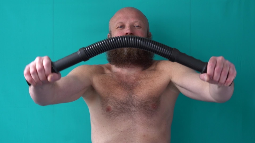 A man with a mustache and a lush beard holds black dumbbells in his hands. A guy with a naked torso is engaged in sports. Bald muscular guy