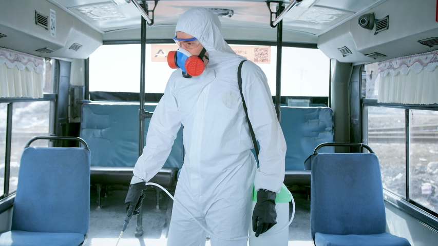 Man disinfect bus covid-19 mers. Corona virus flu disinfection. Coronavirus disinfectant indoors. Worker wear white uniform inside. Protect mask. Spray disinfecter. Danger work. Respiratory face mask. Royalty-Free Stock Footage #1054383119