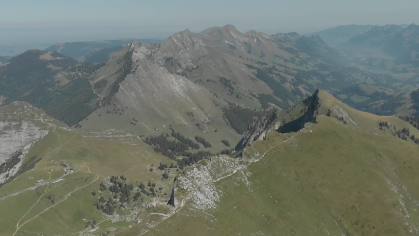 Aerial shot of Alps mountains. They flew on a drone over the mountains, rocks, greenery, over rocky ridges, where there is an untouched nature, a beautiful mountain landscape.