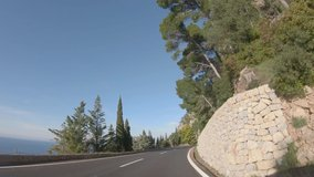 4K point of view footage of car driving on winding road along the coast of Mediterranean sea, cliffs and beautiful mountain landscape. Mallorca island, Spain. Slow motion video during sunny day