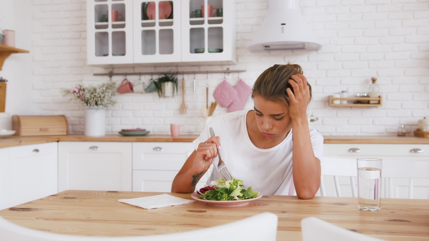 Woman sitting at table, looking sad and bored with diet not wanting to eat salad. Modern kitchen interior. Healthy nutrition, dieting, eating disorder | Shutterstock HD Video #1054385156