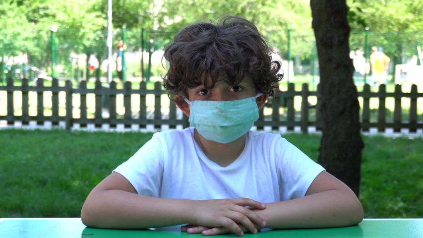 Europe, Italy , Milan - Sad boy with mask  arrives to the park and the play area is closed and empty of children due COVID19 Coronavirus quarantine home lockdown   Royalty-Free Stock Footage #1054385522