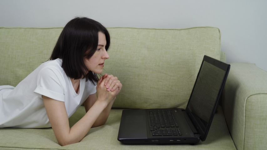 Angry upset young woman user customer using laptop feel frustrated mad about computer problem, worried reading bad news in social media lying down on couch at home. | Shutterstock HD Video #1054385585