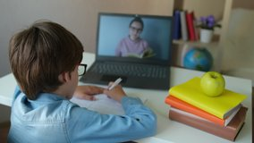 Distance education online learning lesson concept. Child Little school Boy Kid schoolboy children using tablet laptop computer for homework at home. screen monitor Coronavirus COVID-19 quarantine 4 K