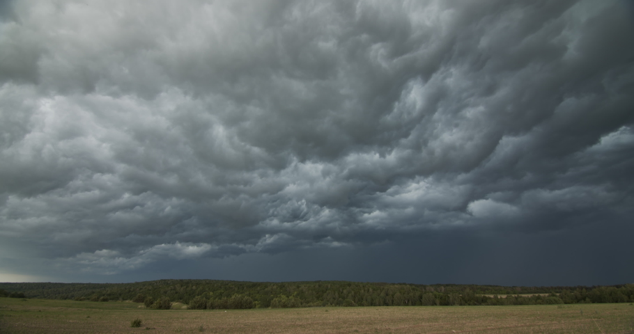 Dark ominous grey storm clouds. Dramatic sky. lighting in dark stormy clouds Royalty-Free Stock Footage #1054388069