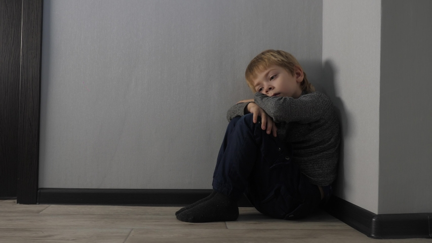 sad upset boy sitting in corner lifestyle . Child punished sitting crying in the corner. Domestic violence concept. Child abuse Royalty-Free Stock Footage #1054389023