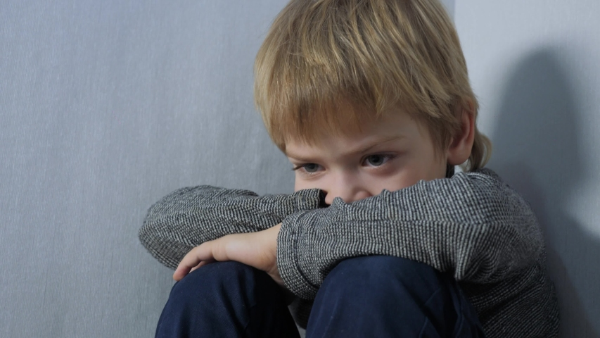 Domestic violence concept the boy is offended . sad upset boy sitting in corner. Child punished sitting lifestyle crying in the corner. Child abuse Royalty-Free Stock Footage #1054389026